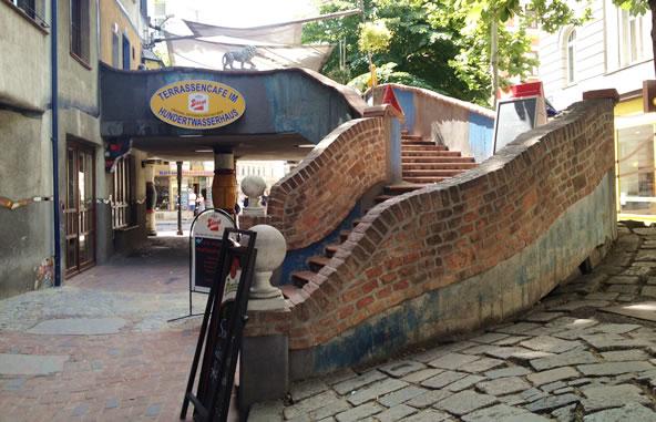 オーストリア/ウィーンにあるフンデルトヴァッサーハウスの外階段とカフェの看板