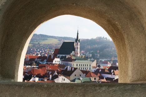クルムロフ城の塀にあるかまぼこ型の穴から見たチェスキークルムロフの景色