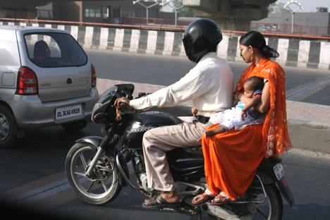バイクの後ろに乗る赤ちゃんを抱いたサリーの女性