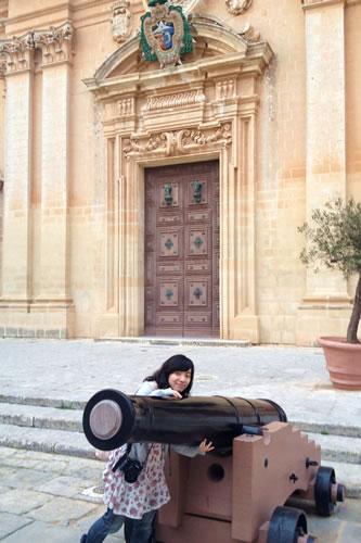 イムディーナの聖パウロ聖堂前の大砲に抱きつく筆者