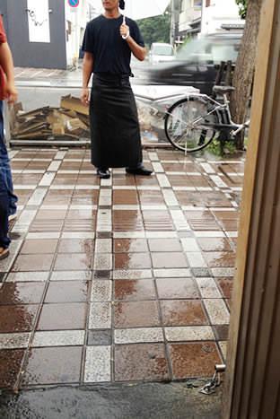 ラーメン東大 大道本店前の道路と雨の中傘をさす店員さん