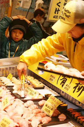 唐戸市場で並べられる寿司とそれを見る少年